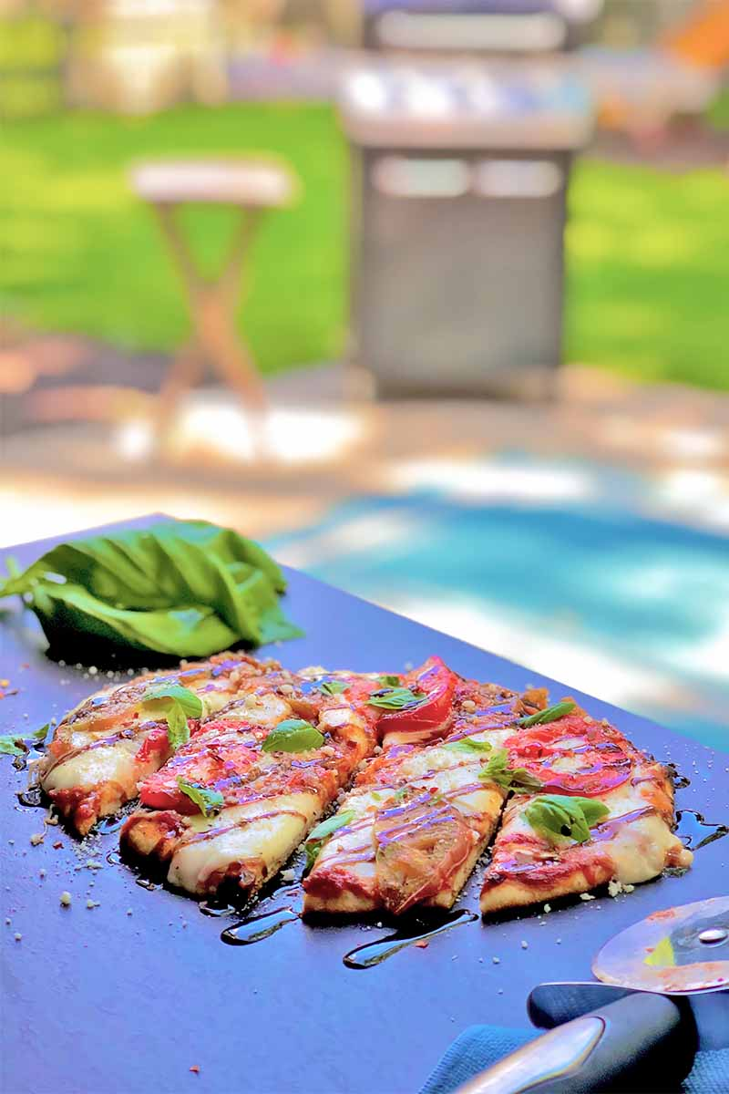 Vertical image of a sliced pizza on a dark surface next to basil and a wheel cutter with a grill in a backyard.