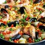 Horizontal image of a pan filled with paella and whole seafood.