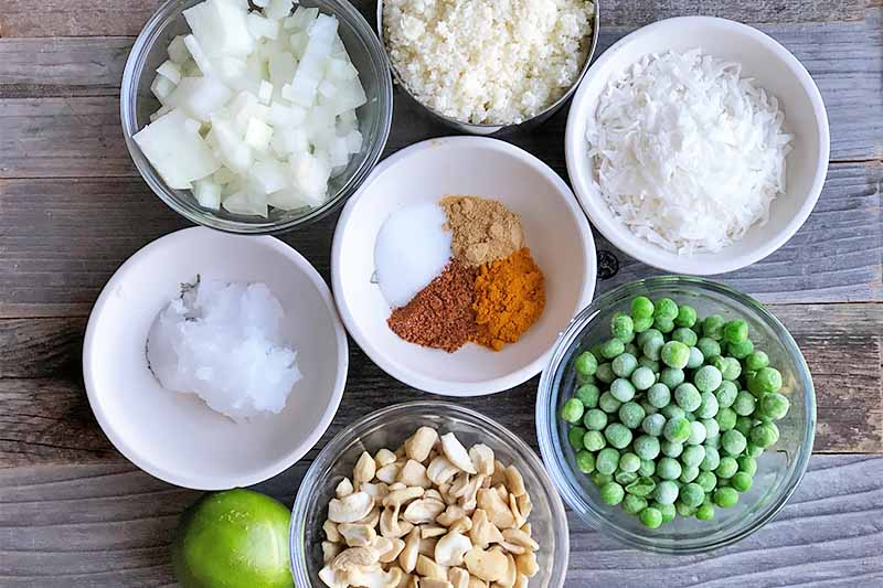 Horizontal image of glass and white bowls filled with diced onion, oil, cashews, peas, shredded coconut, cauliflower, and spices on a wooden surface.