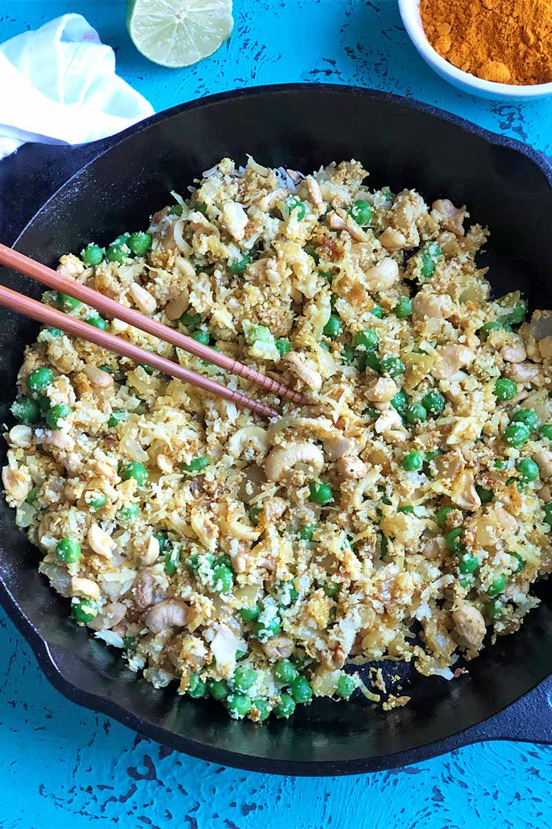 Vertical top-down image of a cauliflower rice mixture and chopsticks in a cast iron pan on a blue surface next to a lime and a white bowl with ground spices.