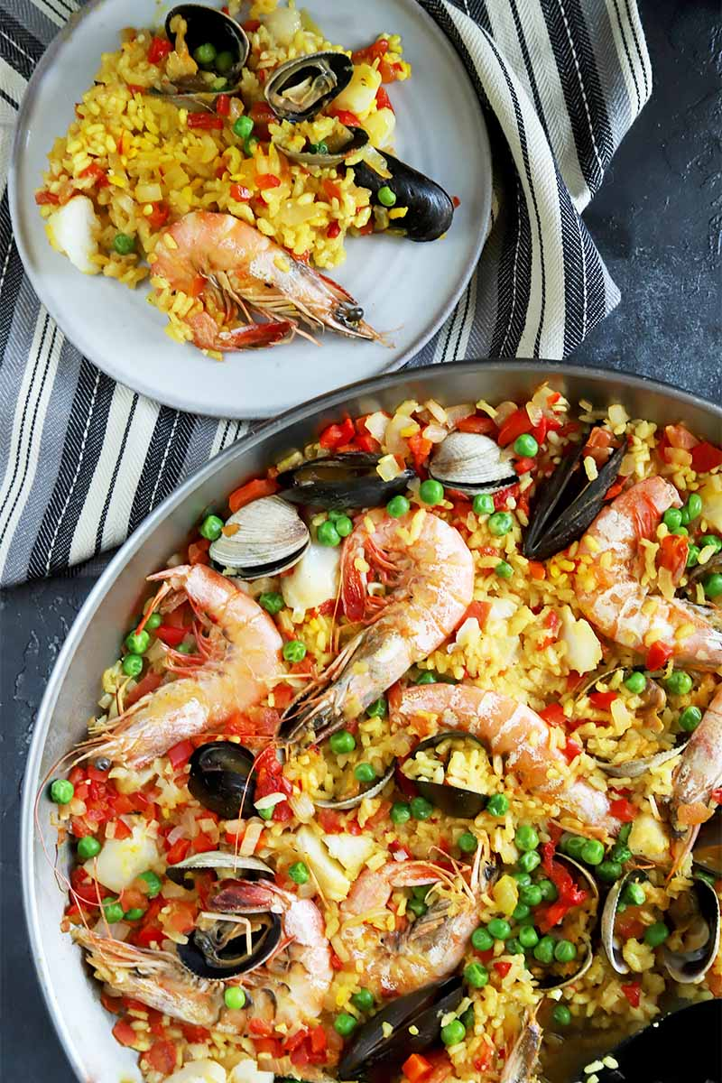 Vertical top-down image of a pan of paella with a plate next to it on a white and black towel.