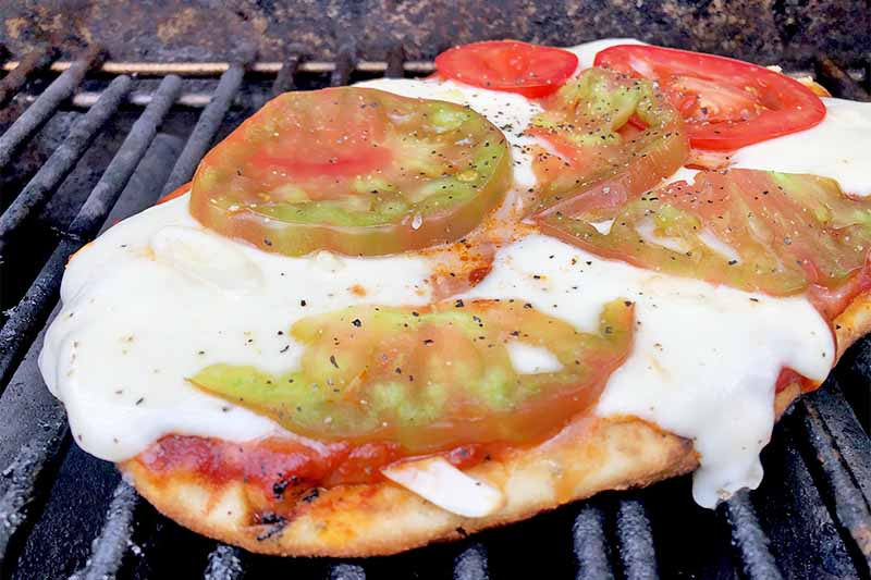 Horizontal image of grilling a flatbread topped with melted cheese and tomato slices.