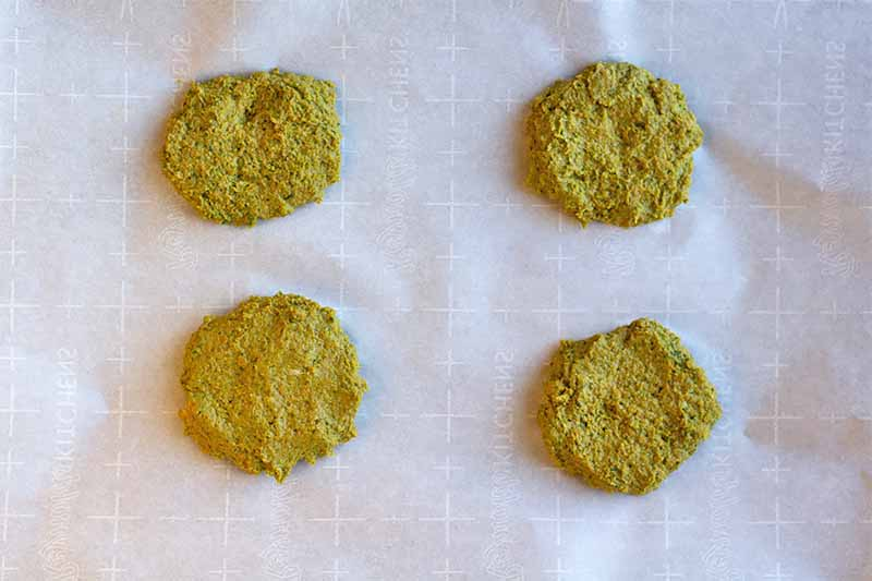 Horizontal image of four green patties on a baking sheet lined with parchment paper.