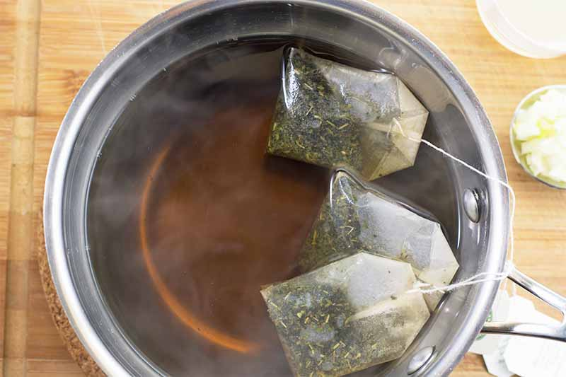 Horizontal image of a pot filled with hot water and tea bags steeping in it on a wooden surface.