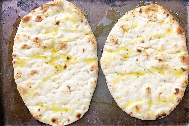 Horizontal image of two flatbreads drizzled with oil on a sheet pan.