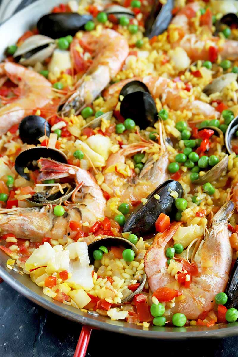 Vertical close-up image of a vibrant paella dish with mixed seafood.