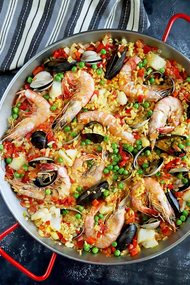 Vertical top-down image of a pan with red handles holding paella with mixed seafood.