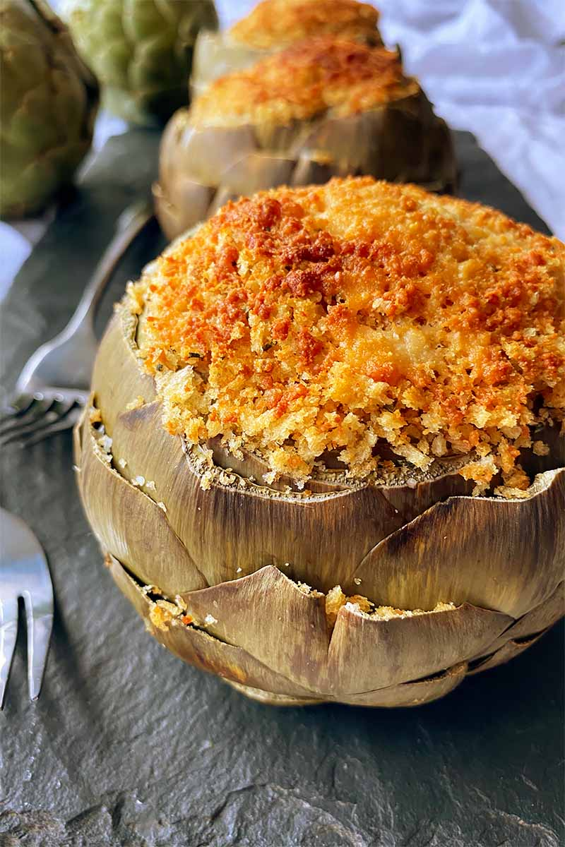 Vertical close-up image of a whole artichoke filled with breadcrumbs on a slate next to metal forks.