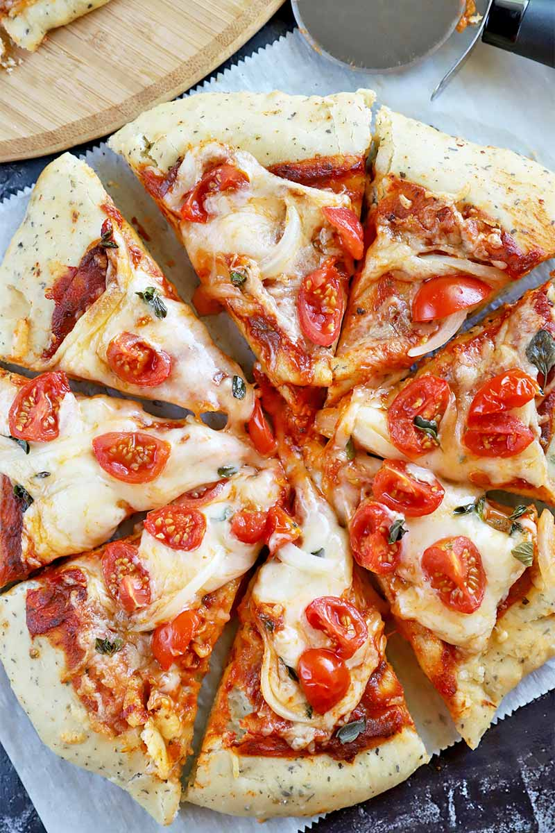 Vertical top-down image of sliced crust topped with tomato sauce, cheese, and tomatoes on parchment paper.
