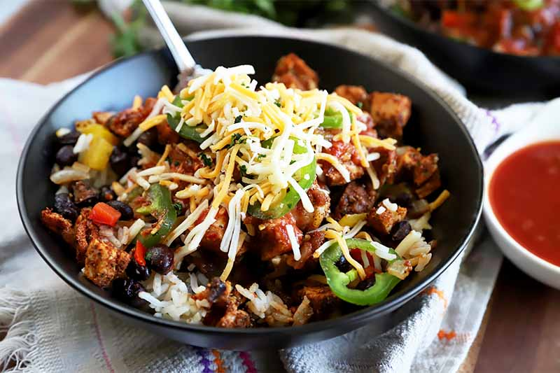 Horizontal image of a black bowl filled with white rice, vegetables, meat, salsa, sliced jalapenos, and shredded cheese on a white towel next to a bowl of salsa.