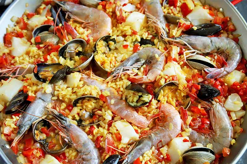 Horizontal image of paella and uncooked whole shrimp.