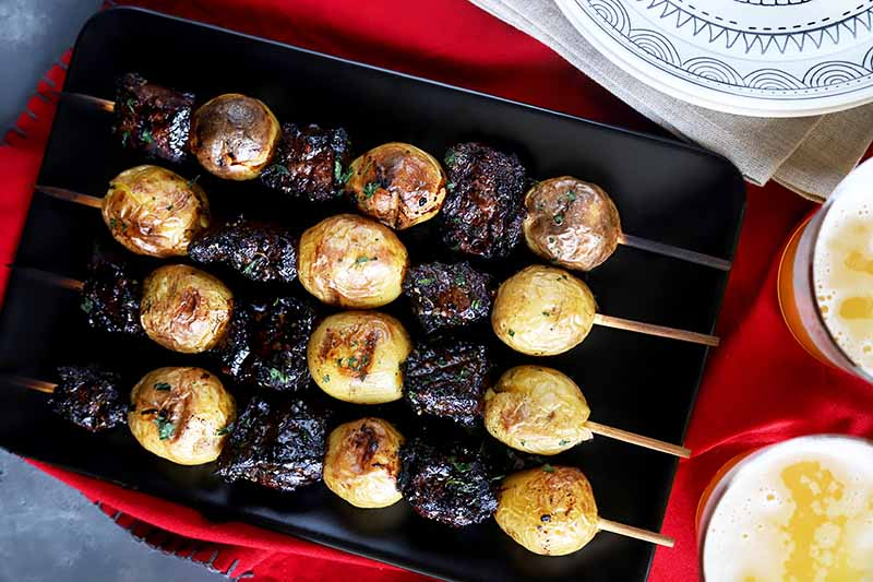 Horizontal image of four grilled meat and potato skewers on a black rectangular plate on a red towel next to two glasses of beer.