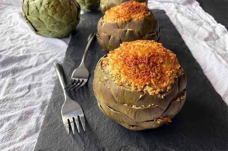 Horizontal image of two whole artichokes with breadcrumbs filling on a dark slate on a towel next to forks.