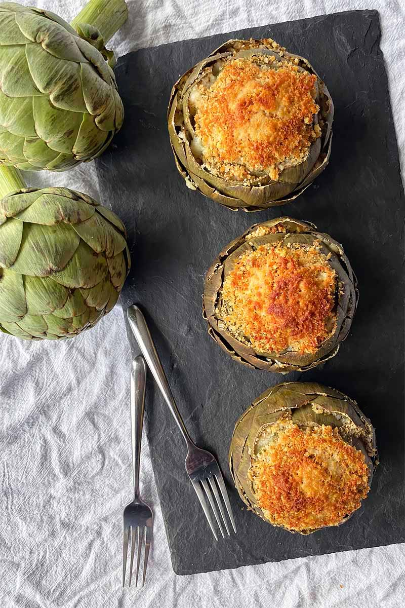 Vertical top-down image of three artichokes with a breadcrumb topping on a slate next to fresh produce and metal forks.