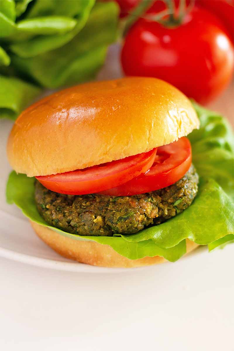 Vertical image of a whole veggie burger with lettuce and tomato on a plate in front of a whole tomato and lettuce.