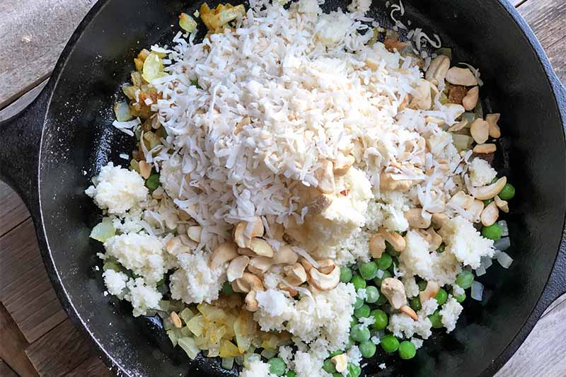 Horizontal image of vegetables, shredded coconut, cashews, and shredded cauliflower in a skillet.