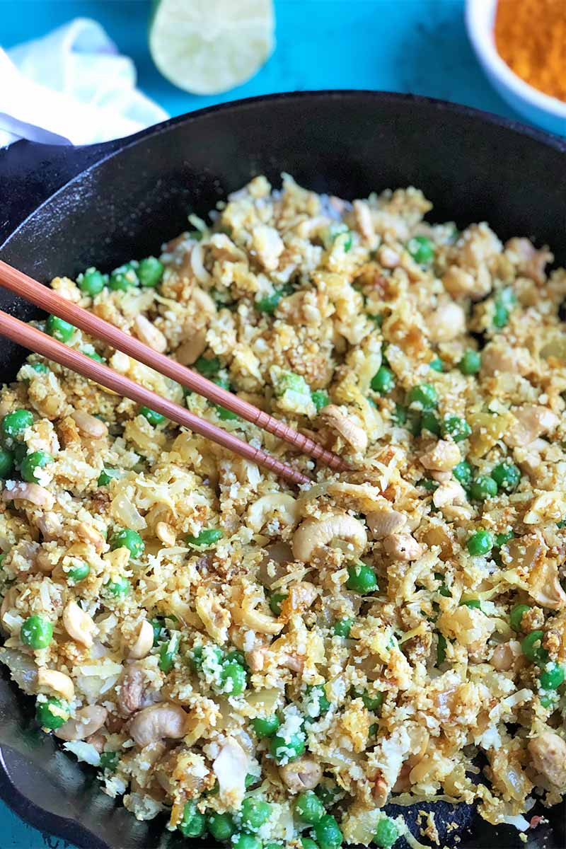 Vertical image of cauliflower rice and green peas mixed in a cast iron skillet with chopsticks inserted into it on a blue surface next to a lime and orange ground spice in a white bowl.
