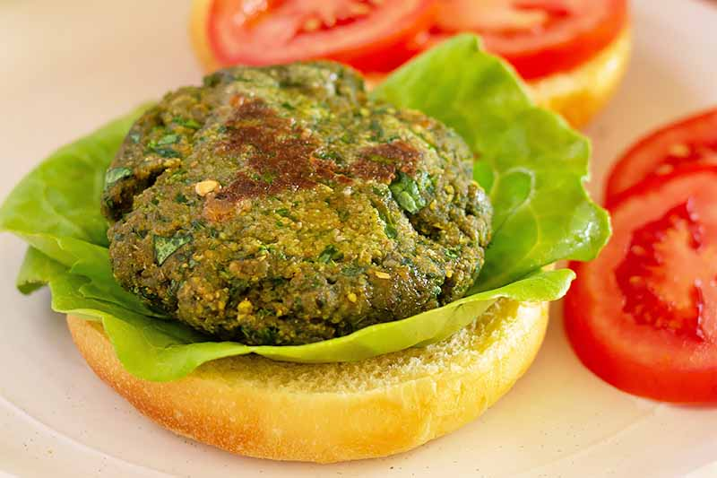 Horizontal image of a green cooked patty on lettuce on a bun next to sliced tomatoes on a white plate.
