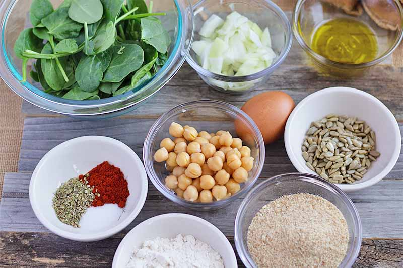 Horizontal image of assorted bowls of fresh produce, beans, dry ingredients, and an egg on a wooden surface.