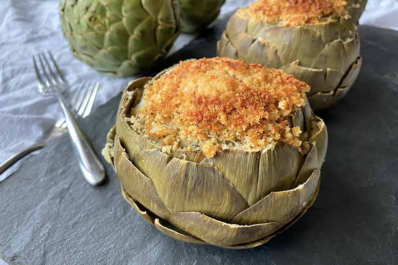 Horizontal image of stuffed artichokes on a slate next to metal forks on a white towel.