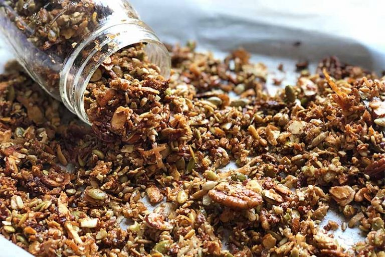 Horizontal image of a glass jar filled with a nut and seed cereal mixture spilling over onto a baking sheet covered in parchment paper.