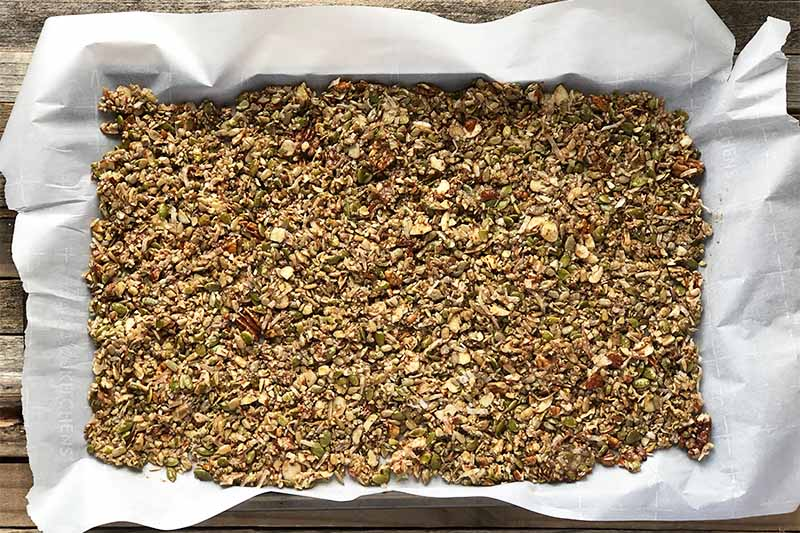Horizontal image of a baking sheet with parchment paper with an uncooked mixed seed and nut mixture spread on it.