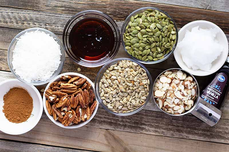 Horizontal image of assorted nuts, seeds, oils, seasonings, and sweeteners in small glass bowls on a wooden table.