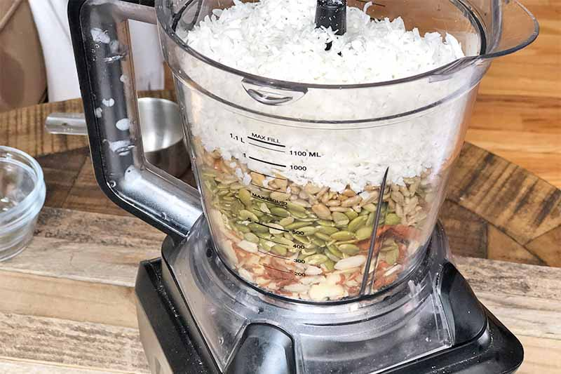 Horizontal image of a food processor with layers of dry ingredients inside.