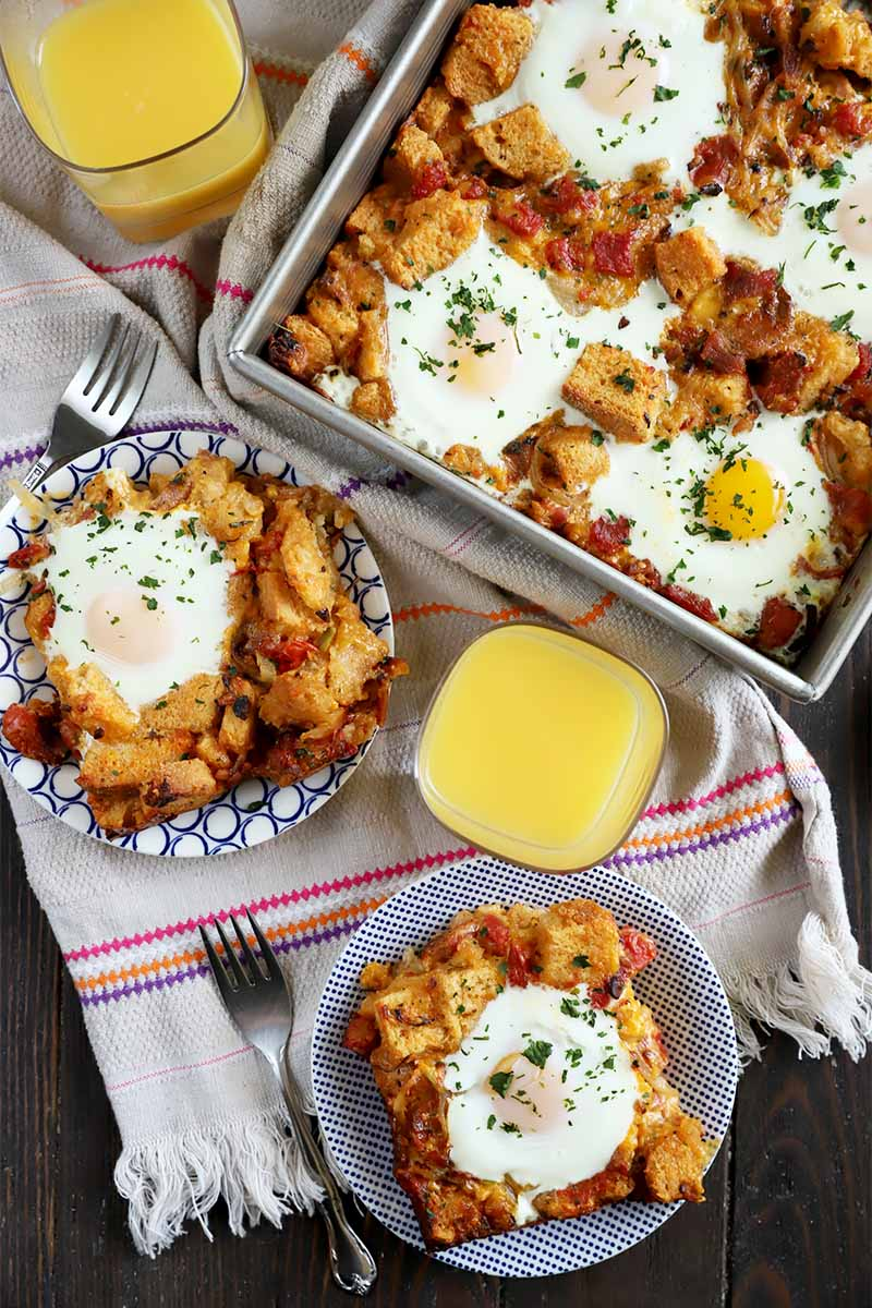 Vertical top-down image of parts of an egg breakfast bake on two plates and in a casserole dish on a towel next to metal forks and orange juice.