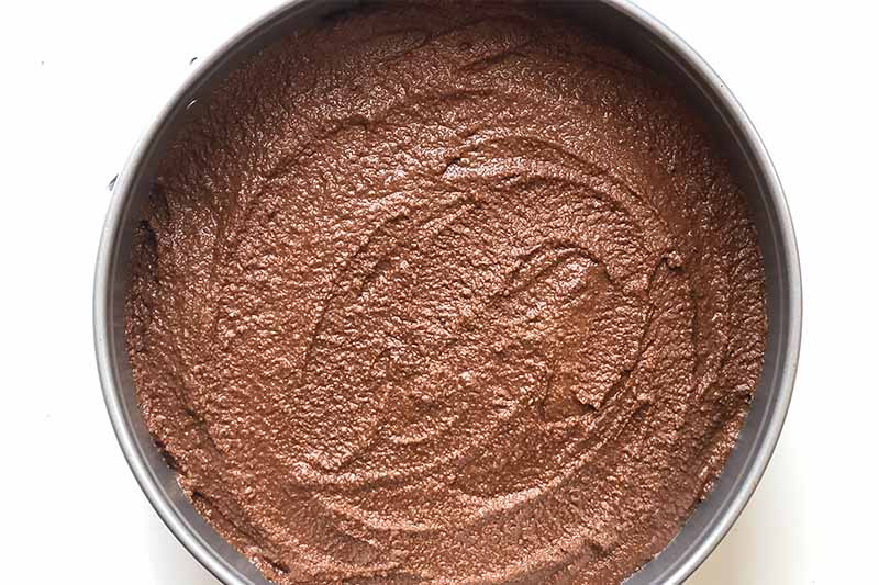 Horizontal image of a thick, slightly grainy light brown mixture in a circular pan.