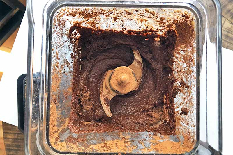 Horizontal image of a blender filled with a messy, thick, wet, grainy brown mixture.