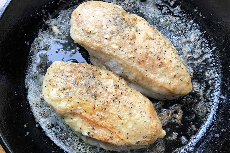 Horizontal image of cooking two poultry breasts in a cast iron pan.