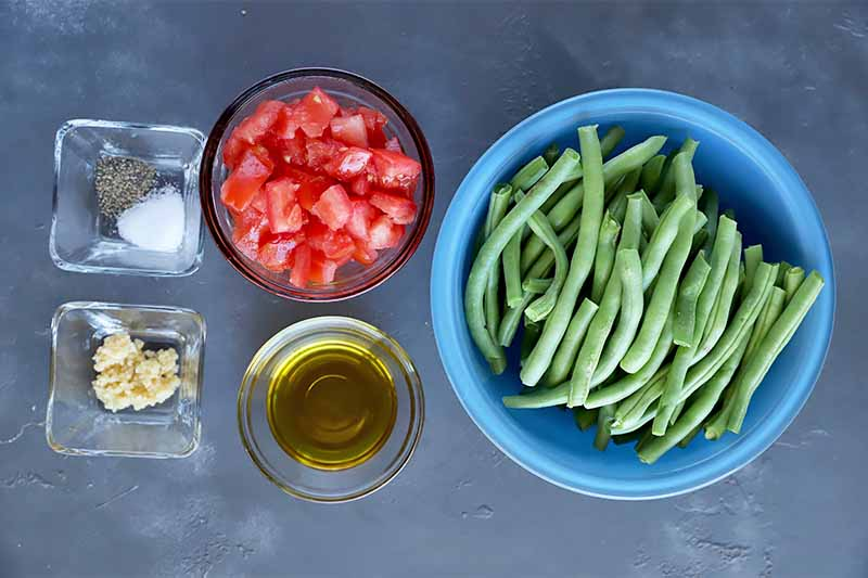 Horizontal image of a blue bowl of green beans, a bowl of tomatoes, and small cups of oil, seasonings, and minced garlic, on a gray surface.