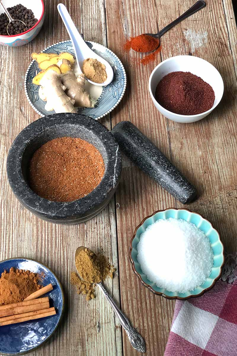 Vertical image of a wooden table with a variety of salts and spices in a variety of bowls and metal spoons, as well as a mortar and pestle with a dark orange spice mixture.