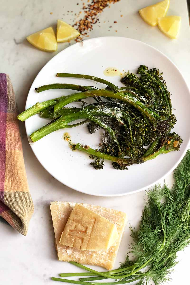Vertical image of a white plate with cooked and seasoned greens next to a checkered towel, cheese rinds, and fresh dill on a marble table.