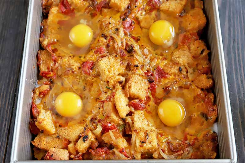 Horizontal image of four uncooked eggs on top of a casserole in a metal rectangular pan.