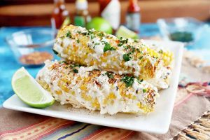 Horizontal image of a stack of elote antojitos on a white plate on a colorful towel in front of assorted condiments and limes.
