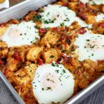 Horizontal image of a breakfast casserole with sunny-side-up eggs.