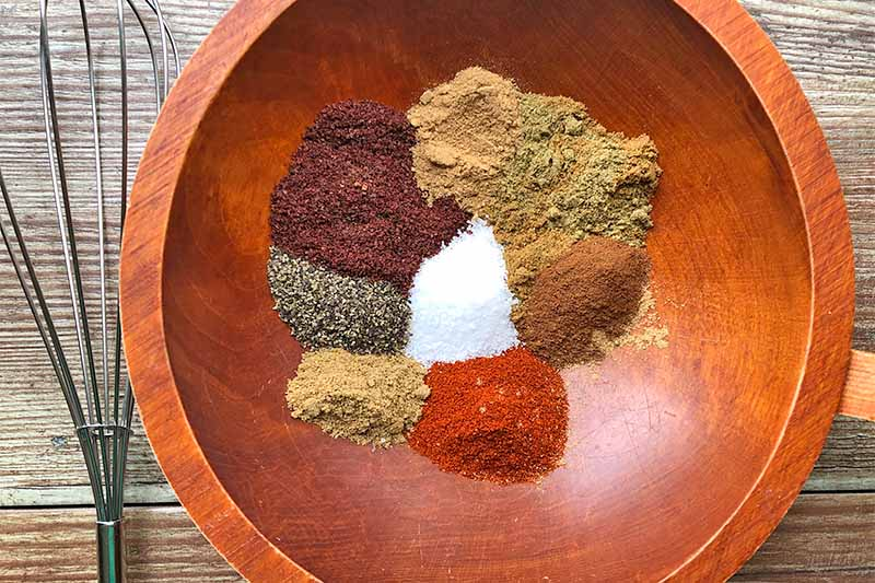 Horizontal image of a wooden bowl with separated mounds of various spices next to a whisk.