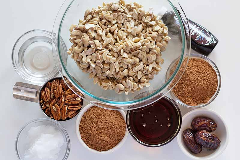 Horizontal image of cashews in a glass bowl surrounded by assorted wet and dry ingredients in glass and ceramic bowls on a white surface.