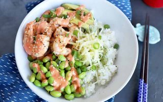 Horizontal image of a white bowl with rice, edamame, and shrimp on a blue napkin next to chopsticks and a red cup.