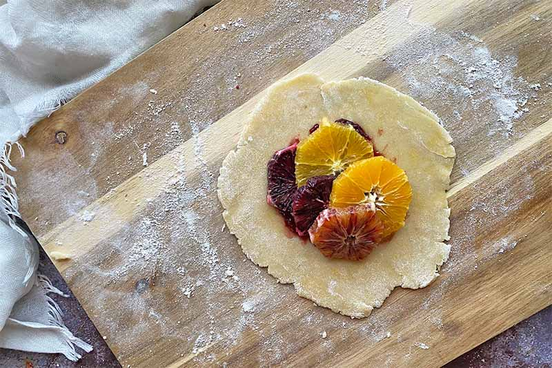 Horizontal image of assembling an open-faced pie filled with sliced oranges.