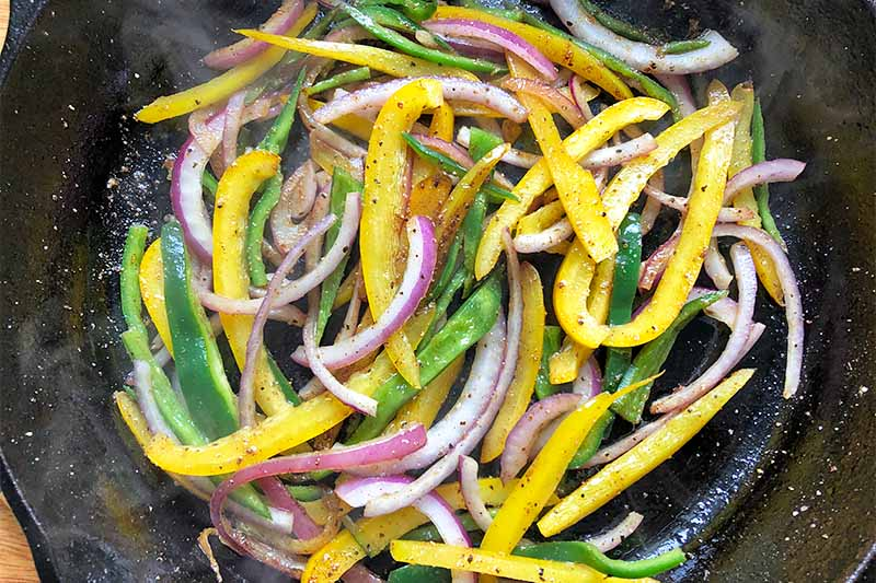 Horizontal image of a pan with sauteed onions and mixed peppers.