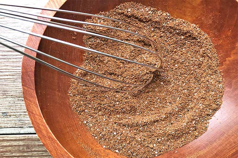 Horizontal image of a wooden bowl filled with a dark orange powdery mixture stirred by a metal whisk.