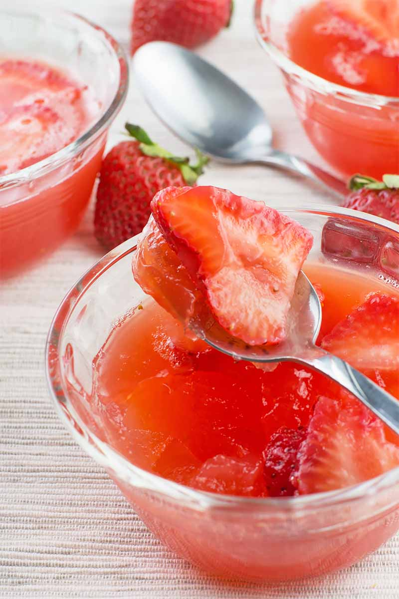 Vertical image of a spoon with a piece of strawberry over a glass bowl with a light red dessert with more of the same dessert in the background.