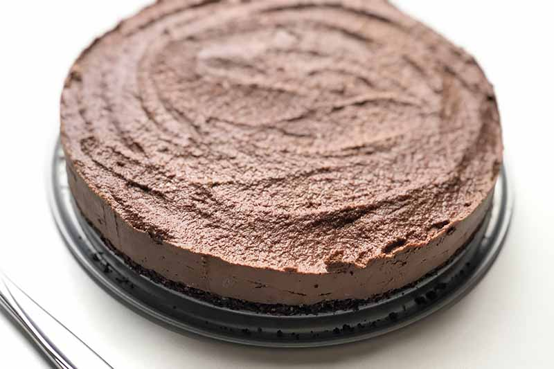 Horizontal image of a circular chocolate dessert on a metal pan on a white table.