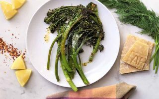Horizontal image of a white plate with cooked and oiled greens next to a checkered towel, fresh dill, rinds, and lemon wedges.