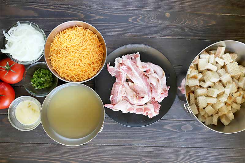 Horizontal image of bowls of prepped and measured uncooked bacon, cubes of bread, shredded cheese, chicken stock, whole tomatoes, herbs, and seasonings on a dark wooden table.