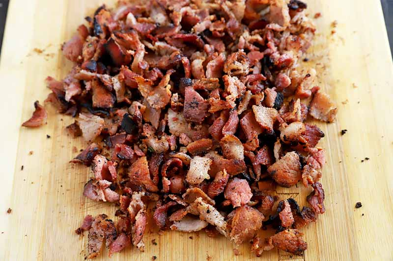 Horizontal image of a wooden table with chopped cooked bacon.