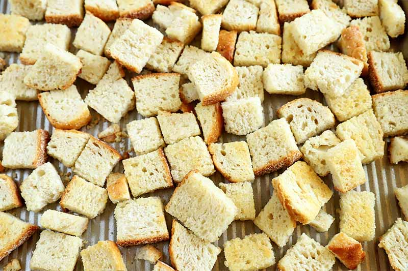 Horizontal image of cubes of breads on a baking sheet.